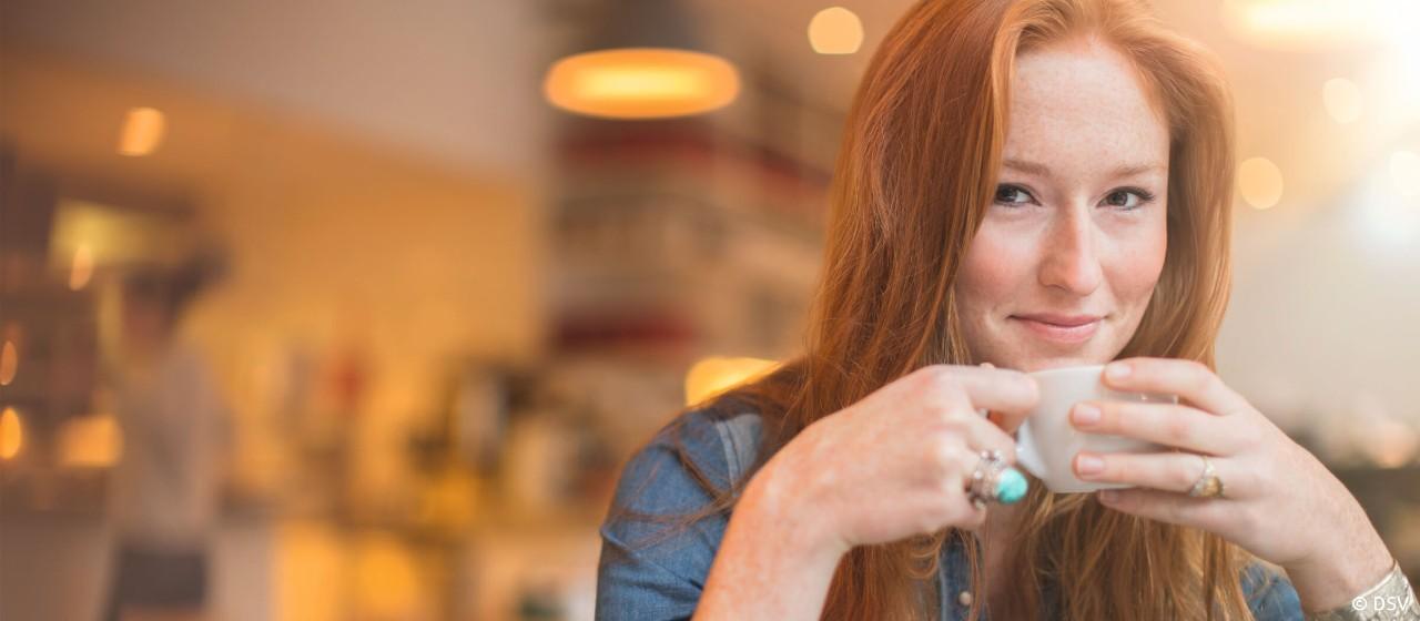 Junge Frau mit einer Kaffetasse in der Hand